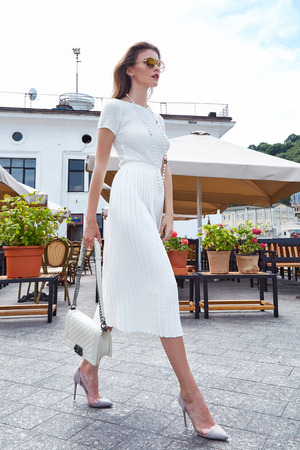 Brunette woman fashion style street look elegant walk cafe restaurant date meeting businesswoman success wear white dress accessory bag sunglasses high-heels shoes clothes summer collection.