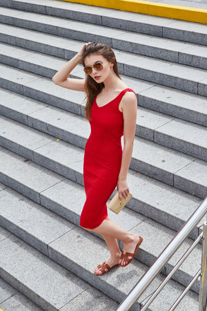 705f23c88 Elegant sexy business woman walk down the stairs on the street summer  weather wear skinny red