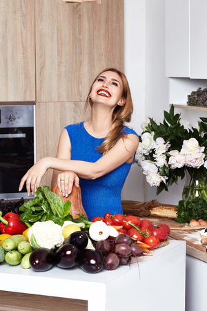 Pretty beautiful woman with white teeth smile wear slim fit blue dress in the kitchen eats sweet tasty cake baking makeup diet right food cook chef housewife lady model culinary.