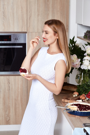 Beautiful young blonde woman wear fashion clothes white slinky dress in the kitchen eats sweet delicious pie with berry baking smile make-up diet right food cook chef housewife romantic evening.