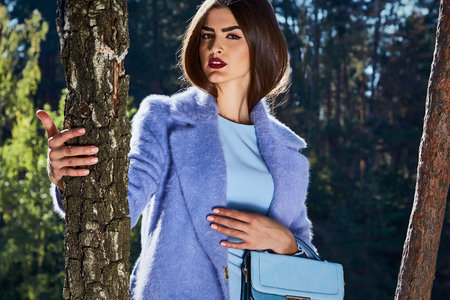 Beautiful sexy woman glamor fashion model wear stylish clothes fall collection accessory handbag shoes forest trees nature sun river walk in the park romantic date female perfect beauty pose