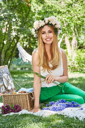Beautiful sexy blond woman happy life style smile, holiday out for a walk in a picnic park in summer garden, model sits on plaid basket with food outdoor recreation warm summer weather flower in hair. Stock Photo