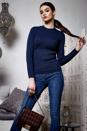 Beautiful sexy woman brunette hair east style arabic morocco furniture glamour model pose fashion clothes skinny denim jeans blue wool sweater accessory hand bag make up pretty face party office.