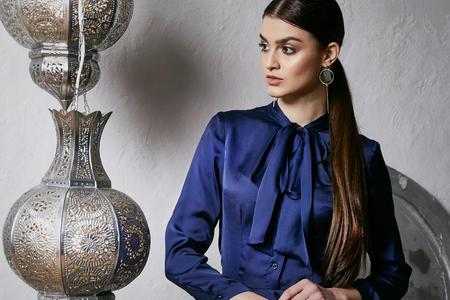 Het mooie sexy van het het oostenstijl van het vrouwen donkerbruine haar Arabische meubilair van de het meubilairglamour stelt manier de kleding van de klerenzijde met zak van de boog de bijkomende hand make-up de kosmetische mooie het bureauruimte van de gezichtspartij. Stockfoto