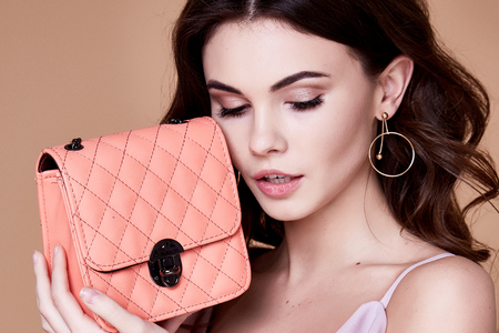 Portrait of beautiful pretty woman makeup face care cosmetic cream lotion plastic surgery accessory bag dress clothes wear style glamour lady mascara beauty salon organic skin brunette hair jewelry. Stockfoto