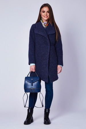 Beautiful sexy attractive young woman with dark hair wearing a strict business suit wool organic coat shoes clothes for autumn walks business meeting accessory lather bag.