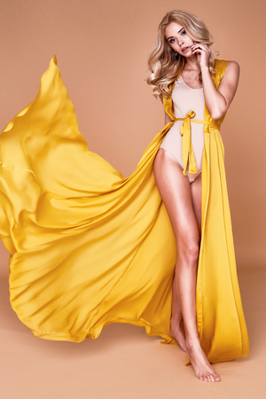 Portrait of beautiful sexy woman blond heir wear long silk dress with swimsuit swimwear perfect body shape diet nutrition organic skin care cosmetic face tan lotion summer vacation fashion model pose. Stock Photo