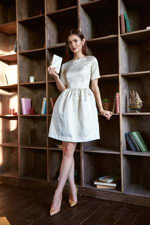 Beautiful business woman lady style perfect body shape brunette hair wear silk white color dress elegance casual style glamour fashion bag accessory shoes jewelry interior library shop cosmetic makeup.