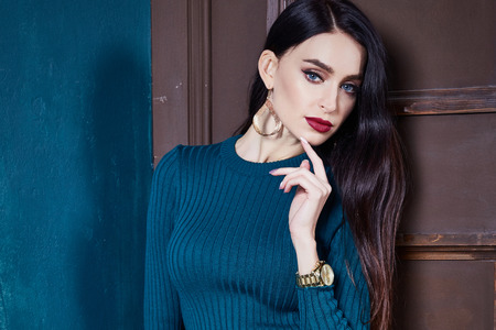 Beautiful business woman lady style perfect body shape brunette hair wear blue color skinny wool dress elegance casual style glamour fashion accessory shoes jewelry earrings interior door.