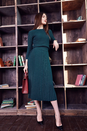 Fashion model beautiful sexy woman brunette hair wear stylish green dress wool sweater skirt casual collection pose studio makeup cosmetic style clothes party accessory bag lady chic vogue library. Stock Photo