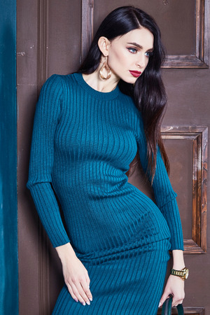 Sexy brunette woman skinny business style dress blue knit perfect body shape diet busy glamour lady casual style secretary diplomatic protocol office uniform hostess etiquette suit interior door. Stock Photo