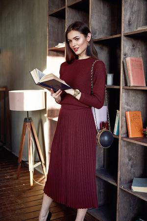 Vrouw zakelijke dame perfecte lichaamsvorm brunette haar dragen rode wollen jurk pak mode stijl elegantie casual mooie model secretaresse lucht stewardess diplomatieke protocol kantoor uniform boek tas.