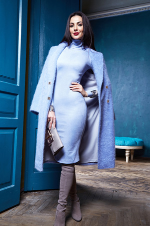 Beautiful sexy woman brunette hair wear fashion clothes business style for office lady trend accessory bag casual glamor natural makeup pretty face interior room door blue color coat jacket outwear. Stock Photo
