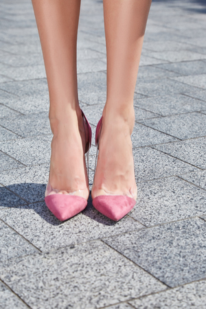Beautiful slender legs tanned skin is shod in high-heeled shoes depilation body care catologue stylish fashion collection walks on the street health body care cream.