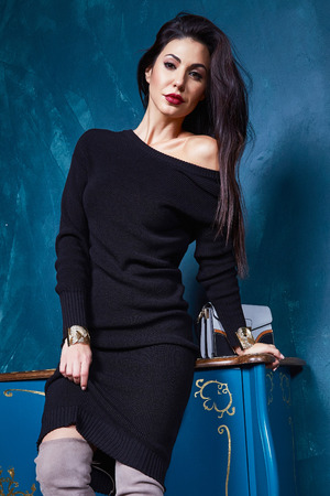 Beautiful sexy woman pretty face makeup wear fashion style clothes black wool dress accessory lather bag and shoes code glamour model office long brunette hair catalog trendy design interior room.