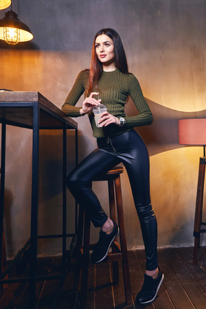 Beautiful sexy woman long brunette hair wear skinny fashion lather black pants and will organic cashmere sweater green color waiting for friend in cafe or pub party meeting interior table light drink.