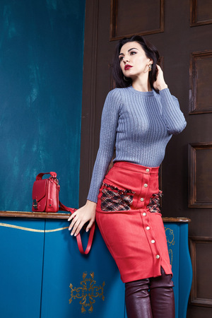Beautiful business woman lady style perfect body shape brunette hair wear red color skirt gray wool sweater elegance casual style glamour fashion brand lather bag accessory shoes jewelry interior.