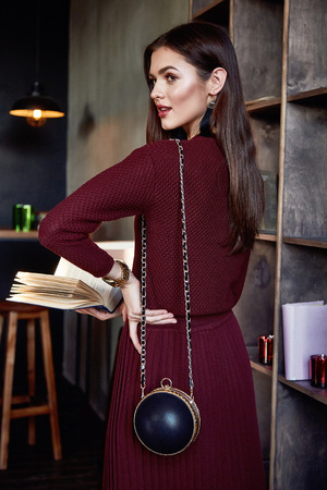 Woman business lady perfect body shape brunette hair wear red wool dress suit fashion style elegance casual beautiful model secretary air hostess diplomatic protocol office uniform book bag. Stock Photo