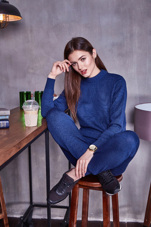 Beautiful sexy woman wear casual suit style fashion organic wool cashmere knitted dark blue color accessory brunette girl makeup in cafe bar drink latte coffee table meeting with friends pretty face.