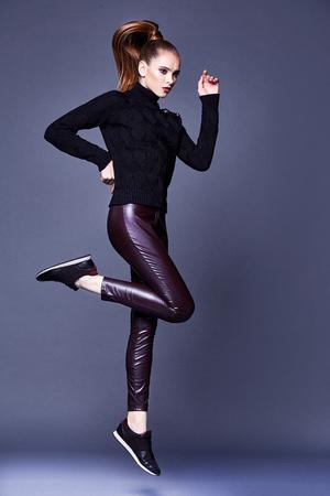 Mooie sexy mooie vrouw perfecte lichaam vorm gezicht make-up dragen zwarte wol kasjmier trui en skinny schuim broek sport schoenen accessoire casual kleding voor partij lopen brunette haarmode stijl. Stockfoto