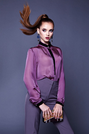 Beautiful business woman lady style perfect body shape brunette jewelry earrings wear fashion clothes lilac silk blouse pants portrait cosmetic make up accessory bag glamour model pose party office. Stock Photo