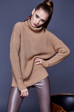 Beautiful woman sexy perfect body shape pretty face makeup wear beige wool cashmere sweater and skinny lather pants shoes accessory casual clothes for party brunette hair fashion model pose style.