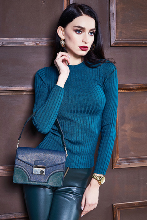 Beautiful sexy young woman brunette hair luxury chic wear casual style for date wool sweater blue color lather pants pretty face autumn collection glamor model fashion clothes interior room brand bag.
