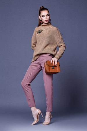 Sexy beautiful woman perfect body shape pretty face make up wear beige wool cashmere sweater and pink pants high heels shoes accessory bag casual clothes for party walk brunette hair fashion style. Фото со стока