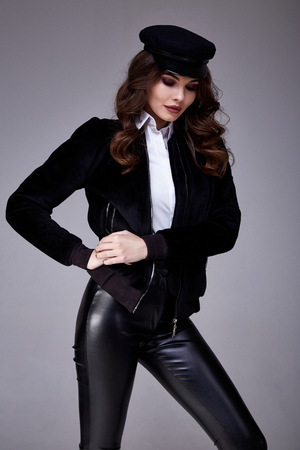 Glamour fashion style catalog casual clothes meeting date walk party sexy beautiful woman brunette hair makeup wear white blouse black lather pants jacket body shape model beauty salon smile hat.