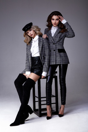 Two sexy beautiful woman blond and brunette curly hair glamour model pose for catalog fashion clothes cotton suit jacket pants hold accessory hat perfect skinny body shape style office party trend. Imagens