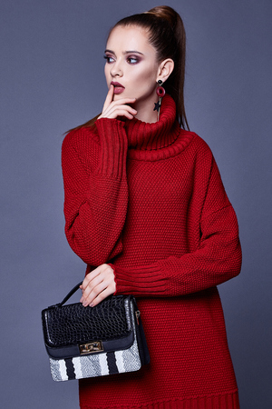 Fashion style woman perfect body shape brunette hair wear red knitted dress wool organic clothes sexy lady casual glamour accessory bag high heels shoes jewelry beautiful face makeup designer.