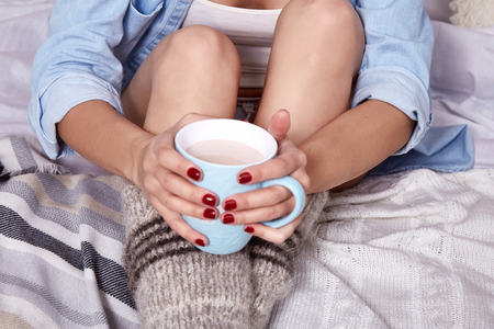 Beautiful Merry Christmas morning brunette woman drink cup sweet hot cacao with marshmallow wear home shirt knitted wool socks plaid New Year eve winter mood nail polish hand manicure.