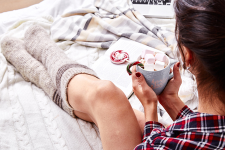 Beautiful Merry Christmas morning brunette woman drink sweet hot cacao with marshmallow eat lollipop candy cane wear home pajamas knitted wool socks watch laptop plaid New Year eve book winter mood. Stock Photo