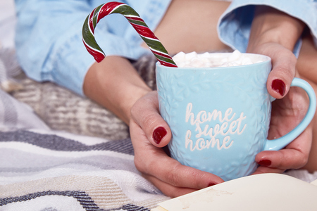 Beautiful Merry Christmas morning woman drink sweet hot cup cacao marshmallow eat lollipop candy cane wear home knitted wool socks plaid New Year eve read book winter mood nail polish hand manicure.