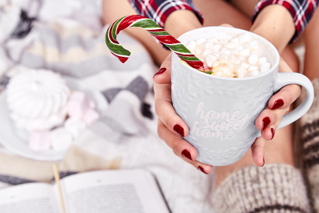 Beautiful Merry Christmas morning brunette woman drink sweet hot cacao marshmallow eat lollipop candy cane wear home pajamas knitted wool socks plaid New Year eve read book winter mood nail polish.