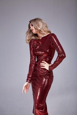 Beautiful sexy woman wear lux skinny shine red dress shiny sequins style for party celebrate New Year Christmas beauty salon hair style makeup perfect body shape jewelry model pose fashion clothes. Stock Photo
