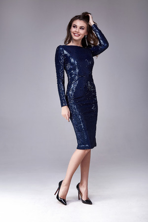 Beautiful sexy woman wear lux skinny blue dress shiny sequins style for party celebrate New Year Christmas beauty salon hair style makeup perfect body shape jewelry model pose fashion clothes glamour. Imagens