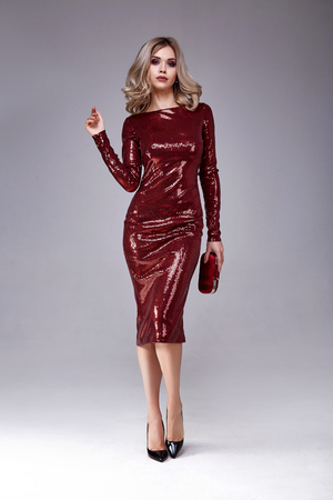 Beautiful sexy woman wear lux skinny shine red dress shiny sequins style for party celebrate New Year Christmas beauty salon hair style makeup perfect body shape jewelry model pose fashion clothes. Archivio Fotografico