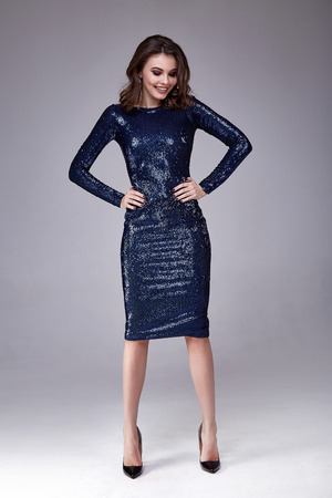 Beautiful sexy woman wear lux skinny blue dress shiny sequins style for party celebrate New Year Christmas beauty salon hair style makeup perfect body shape jewelry model pose fashion clothes glamour. Stock Photo