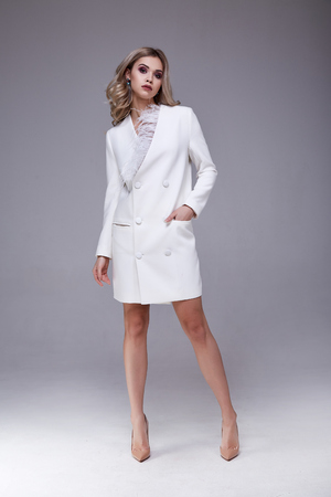 Sexy pretty beautiful woman fashion style clothes model perfect face white coat silk curly blond hair luxury glamour outwear jacket dress code businesswoman jewelry accessory catalog beauty salon party.