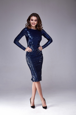 Beautiful sexy woman wear lux skinny blue dress shiny sequins style for party celebrate New Year Christmas beauty salon hair style makeup perfect body shape jewelry model pose fashion clothes glamour. Banco de Imagens