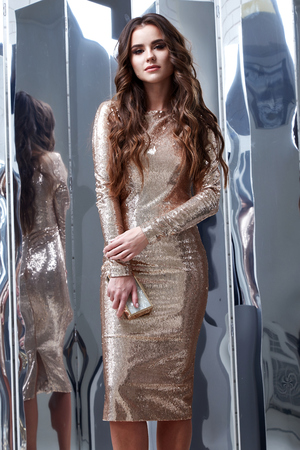Sexy beautiful woman wear lux skinny shine gold dress shiny sequins style for party celebrate New Year Christmas beauty salon hair makeup perfect body shape jewelry model pose fashion clothes clutch.