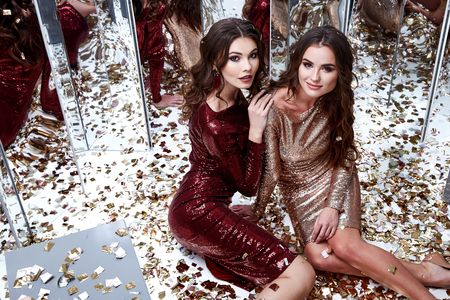 Two sexy beautiful woman wear skinny gold red dress shiny sequins style party celebrate New Year Christmas beauty salon brunette hair makeup jewelry model lux fashion clothes glamour sit on the floor.
