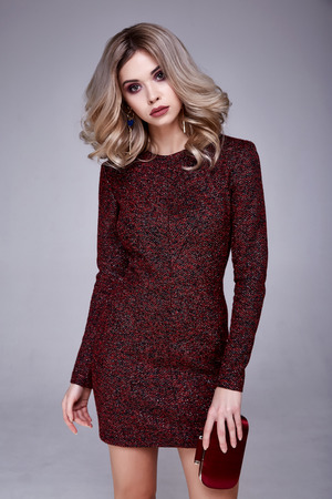 Beautiful sexy woman pretty face makeup wear fashion style clothes red wool dress accessory lather shoes code glamour model office long blonde hair catalog trendy design businesswoman elegant bag leg. Stock Photo