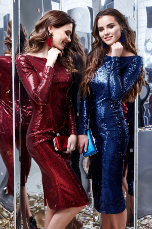 Two beautiful sexy woman friend wear lux skinny shine blue and red dress shiny sequins style party celebrate New Year Christmas beauty salon hair makeup accessory jewelry model pose fashion clothes.