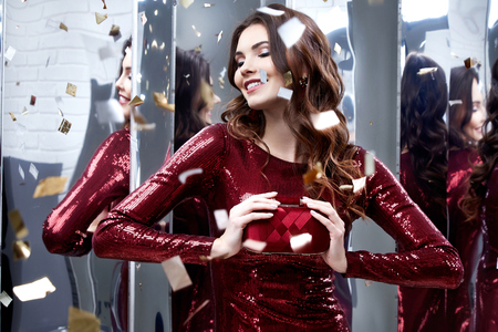 Beautiful sexy woman wear lux skinny shine red dress shiny sequins style for party celebrate New Year Christmas beauty salon hair style makeup perfect body shape jewelry model pose fashion clothes. Banco de Imagens