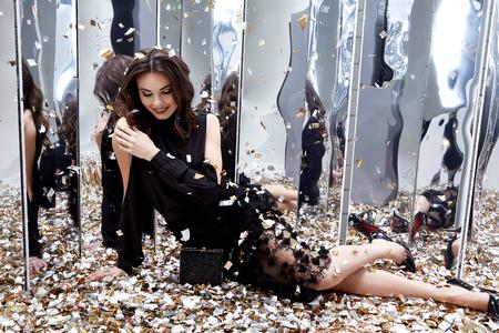 セクシーなかわいい女性は、金色のスパンコールグラマーファッションモデル明るいメイクアップ香水の多くを床に座って、黒のスタイリッシュな