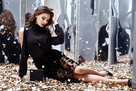 Sexy pretty woman sit floor with lot of golden sequins glamour fashion model bright makeup perfume wear black stylish dress celebration party holiday beauty salon Christmas Birthday girl Valentine's. Stock Photo