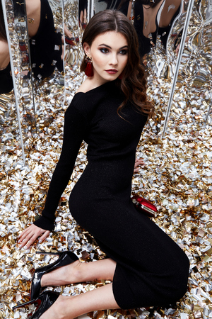 Beautiful sexy woman brunette hair evening makeup pretty face wear luxury black dress skinny fit style celebrate party holiday Christmas New Year mirror shiny sequins accessory earrings bag shoes.