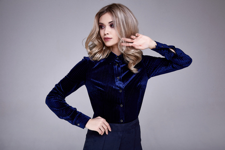 Portrait of beautiful business woman lady style perfect body shape brunette jewelry wear fashion clothes blue silk blouse pants cosmetic make up accessory glamour model pose party office chair.